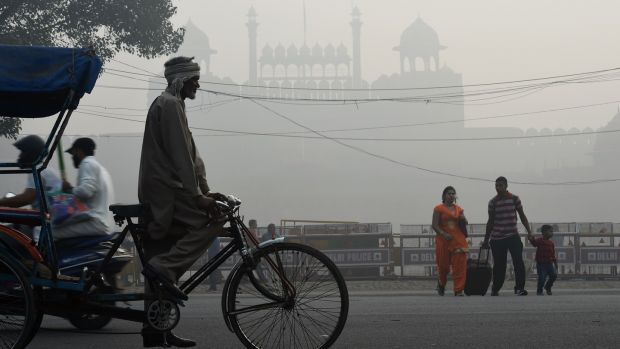 An Indian family crosses a road amid heavy smog in front of the Red Fort in New Delhi on Friday. Photograph: Prakash Sing/AFP/Getty Images