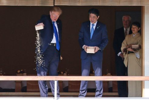 US president Donald Trump pours out the remaining  fish food from a container as he feeds carp at a koi pond with Japan's prime minister Shinzo Abe. Photograph: Toru Hanai/AP