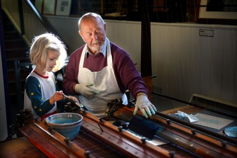 MACHINES FROM THE PAST: Freya Leathley Barthel (6), of Raheny, with Don Kerrigan, Churchtown, using a pen ruling machine at Printfest in the National Print Museum, Dublin, as part of Science Week 2017. Photograph: Dara Mac Dónaill/The Irish Times