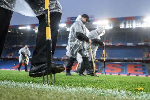 WORLD CUP PLAYOFF: Stadium staff test the pitch with spades under pouring rain ahead of the Fifa 2018 World Cup play-off second leg qualifying match between Switzerland and Northern Ireland at St Jakob-Park stadium in Basel, Switzerland. Photograph: Fabrice Coffrini/AFP/Getty Images