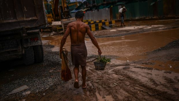 A construction worker heads back to his shipping container room after catching dinner in the Mekong river in April 2017. It's not uncommon for labourers to live onsite, but conditions are poor and overcrowded. Photograph: Lauren Crothers