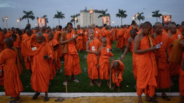 Monks checking their phones after a prayer ceremony during which the ashes of late King Norodom Sihanouk were interred in July 2014 at the Royal Palace in Phnom Penh. Photograph: Lauren Crothers