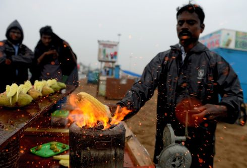 MONSOON RAINS: An Indian vendor roasts corn at Marina Beach during heavy monsoon rains in Chennai. Photograph: Arun Sankar/AFP/Getty Images