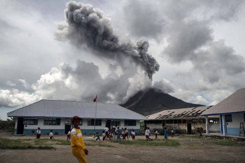 PLAY WITH FIRE: Children play at an elementary school as the Mount Sinabung volcano spews smoke in Karo, Indonesia. Photograph: Ivan Damanik/AFP/Getty Images