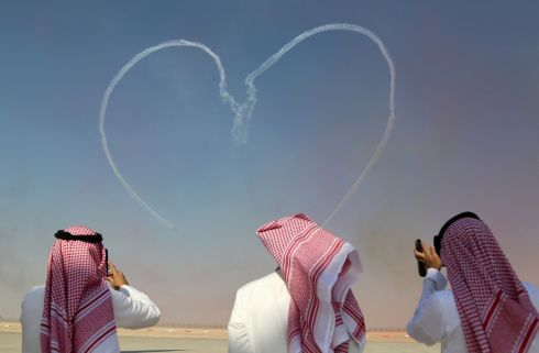 LIGHT-HEARTED: Visitors take pictures as the Al Fursan aerobatic team of the UAE Air Force performs during the Dubai Airshow. Photograph: Satish Kumar/Reuters