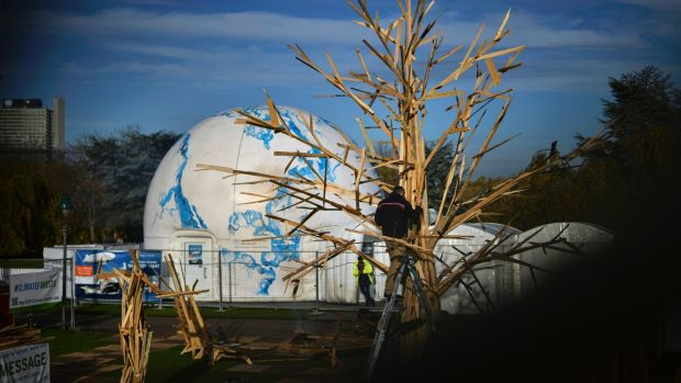 A craftsman adds parts to a sculpture, Climate Tree, during the UN Climate Change Conference COP23 in Bonn, Germany, today. Photograph: Philipp Guelland/EPA