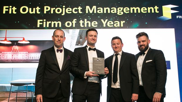 Trevor Schwer, MD, The Interiors Group, presents the Fit Out Management Firm of the Year award to the Turner & Townsend team