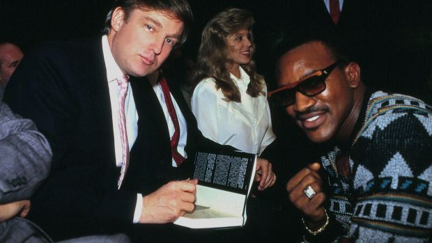 Donald Trump signs his book The Art Of The Deal for boxer Evander Holyfield in Atlantic City, New Jersey in 1989. Photograph: Jeffrey Asher/ Getty Images