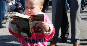 Grace Mahoney, 16 months, looks at a copy of The Art of the Deal before  a Donald Trump rally  in Portsmouth, New Hampshire last year. Photograph: Mary Schwalm/AFP/Getty Images