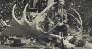 Grandfather James Michael Duffy and his house are diminished to Lilliputian proportions by the presence in the foreground of the skull and antlers of a giant Irish deer'