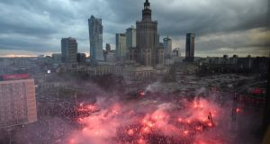 Polish nationalists lit flares as they took part in a demonstration under the slogan 'We want God' as part of Polish Independence Day celebrations in Warsaw on Saturday. Photograph: Radek Pietruszka/EPA