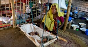 A Rohingya Muslim woman rocks a cradle with her one-month-old son Mahafuzur Rahman at Thaingkhali refugee camp in Ukhiya, Bangladesh on Tuesday.   Photograph: AM Ahad/AP