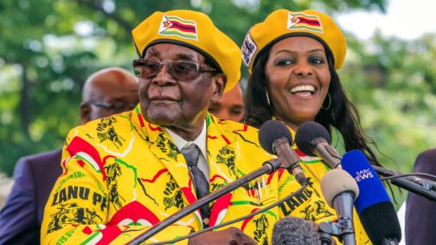 Zimbabwe president: Robert Mugabe addresses Zanu-PF members gathered to show support for his wife, Grace (right), becoming the party's next vice-president. Photograph: Jekesai Njikizana/AFP/Getty