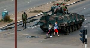 Women walk past an armoured personnel carrier by an intersection in Harare.  Photograph: Jekesai Njikizana/AFP/Getty Images