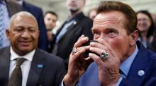 Good kava: Arnold Schwarzenegger helps himself to a plant-based beverage in the company of Fijian prime minister Frank Bainimarama. Photograph: Reuters/Wolfgang Rattay