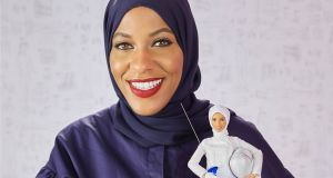 US Olympic fencer Ibtihaj Muhammad holding the first hijab-wearing Barbie based on her to be released in 2018, in New York City. Photograph: EPA/Mattel