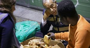 Portuguese president Marcelo Rebelo de Sousa, with the help of volunteers, gives food to a homeless man living in the streets of Lisbon, Portugal, this week. Photograph:José Sena Goulao/EPA