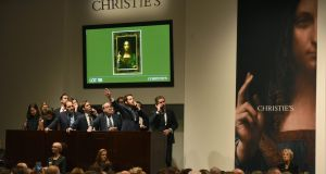 Christie's employees take bids for Leonardo da Vinci's Salvator Mundi during the postwar and contemporary art evening sale at Christie's New York on Wednesday. Photograph: Timothy A Clary/AFP/Getty Images