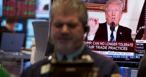 Traders on the floor of the Dow Industrial Average at the New York Stock Exchange in New York, as  Donald Trump delivers a televised statement from the White House.  Photograph:  Bryan R Smith/AFP/Getty Images