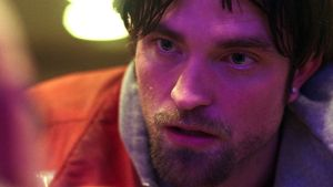 Robert Pattinson in Good Time: his hair is yellowed to the colour of diseased liver, his eyes suspiciously unblinking