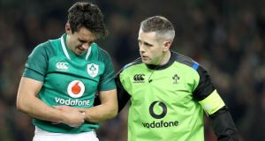 Ireland's Joey Carbery leaves the field in pain with Dr Ciarán Cosgrove after fracturing his left forearm. Photograph: Dan Sheridan/Inpho