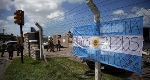 An Argentine national flag hangs on a fence at the entrance of the Argentine Naval Base where the missing at sea ARA 'San Juan' submarine sailed from, in Mar del Plata, Argentina. Photograph: Marcos Brindicci/Reuters