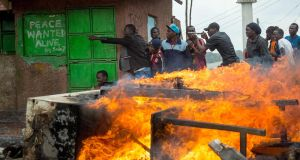 NAIROBI PROTEST: Supporters of Kenya's opposition party, the National Super Alliance, demonstrate next to a fire in Kibera slum, Nairobi, after the Supreme Court dismissed two petitions to overturn the October 26th presidential election re-run, validating the poll victory of President Uhuru  Kenyatta. The court decision led to celebrations in ruling party strongholds. Photograph: Georgina Goodwin/AFP/Getty Images
