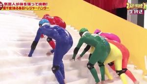 'Slippery Stairs': Men, barefoot, in rubber onesies climbing a stairs made of ice. What's not to like?