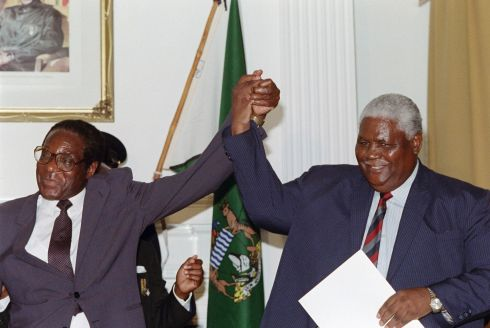 "This file photo taken on December 22, 1987 shows Zimbabwe's President Robert Mugabe (L) and former President of Zimbabwe African People's Union (ZAPU) Joshua Nkomo raising their fists in Nairobi.  Robert Mugabe resigned as president of Zimbabwe on November 21, 2017, parliament speaker Jacob Mudenda told lawmakers, ending a 37-year rule defined by brutality and economic collapse. ""I Robert Gabriel Mugabe in terms of section 96 of the constitution of Zimbabwe hereby formally tender my resignation... with immediate effect,"" said speaker Mudenda, reading the letter.  / AFP PHOTO / ALEXANDER JOEALEXANDER JOE/AFP/Getty Images"