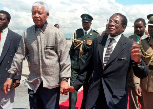 Zimbabwe's President Robert Mugabe holds hands with his then South African counterpart Nelson Mandela, greeting him on his arrival to Harare, Zimbabwe December 13, 1998. REUTERS/Howard Burditt/File Photo