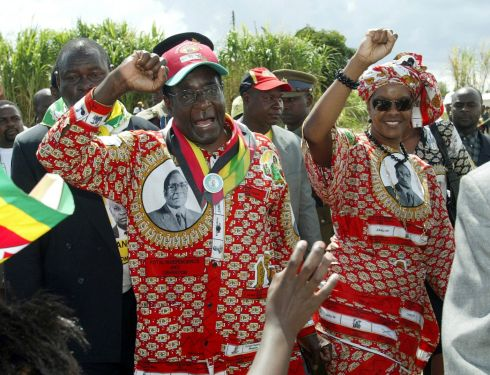 Zimbabwe's President Robert Mugabe and his wife Grace greet ruling ZANU (PF) supporters on their arrival at an election rally in Chivu, Zimbabwe March 28, 2005. REUTERS/Howard Burditt/File Photo