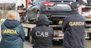 Criminal Assets Bureau raid: officers with some of the vehicles seized in Killarney, Co Kerry, on Tuesday morning. Photograph: Press 22