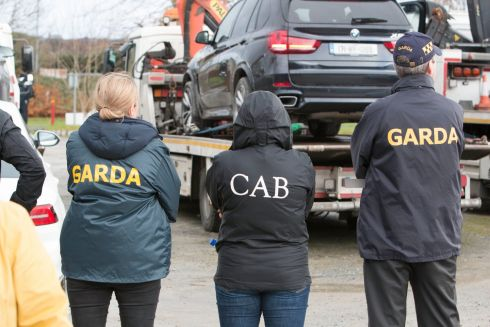 PLANNED RAIDS: Members of the Criminal Assets Bureau (CAB) and armed gardaí during the seizure of an estimated half a million euro worth of vehicles and €100,000 in cash during planned raids in Killarney, Co Kerry. Photograph: Press 22