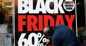 An international affair: A worker places a sign  announcing Black Friday sales at a shop in Valencia, Spain, today. Photograph: Juan Carlos Cardenas/EPA
