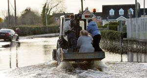 Residents take a lift on a tractor up Manor Road in Mountmellick where up to half a meter of water entered  homes in the area  on  Wednesday afternoon and evening.  Photograph: Alan Betson / The Irish Times