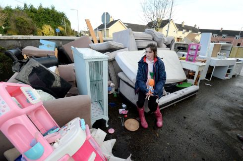 WASHED OUT: Ita Conroy looks at the water-damaged contents of her home near the Manor Road in Mountmellick after up to half a meter of water entered her family's home on Wednesday. Photograph: Alan Betson/The Irish Times