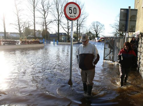 People walk through flood water in Mountmellick, Co Laois, after three rivers burst their banks and flooded dozens of homes. Photograph: Brian Lawless/PA Wire