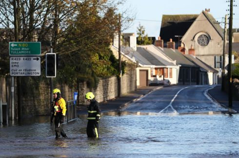 Members of the fire service walk through flood water in Mountmellick, Co Laois. Photograph: Brian Lawless/PA Wire