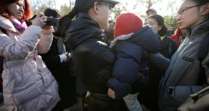 A parent is surrounded by members of the media outside the kindergarten run by pre-school operator RYB Education  in Beijing, China. Photograph: Jason Lee/Reuters