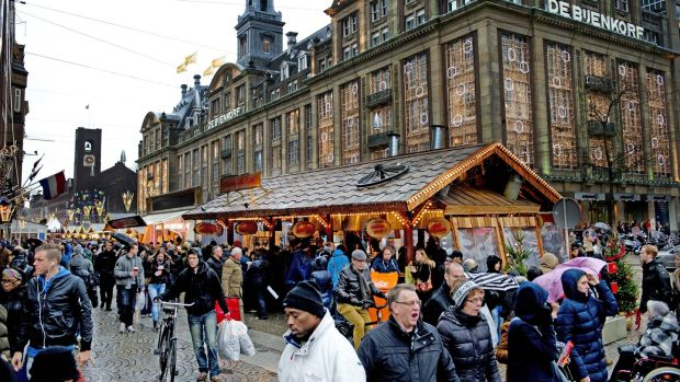 People shop at a Christmas market in the centre of Amsterdam. Photograph: Robin Utrectht/AFP/Getty