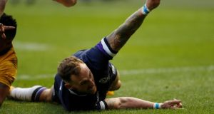 Scotland's Byron McGuigan scores the first try of the game. Photograph: Russell Cheyne/Reuters