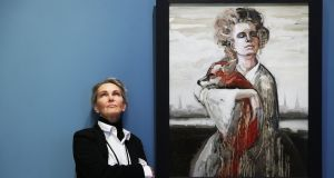 Zane Sutra beside her portrait on the wall of the National Gallery of Ireland as part of the Hennessy Portrait Prize. Photograph: Leon Farrell/Photocall Ireland.