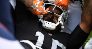 Michael Crabtree has his helmet pulled off by Aquib Talib. Photograph: Robert Reiners/Getty