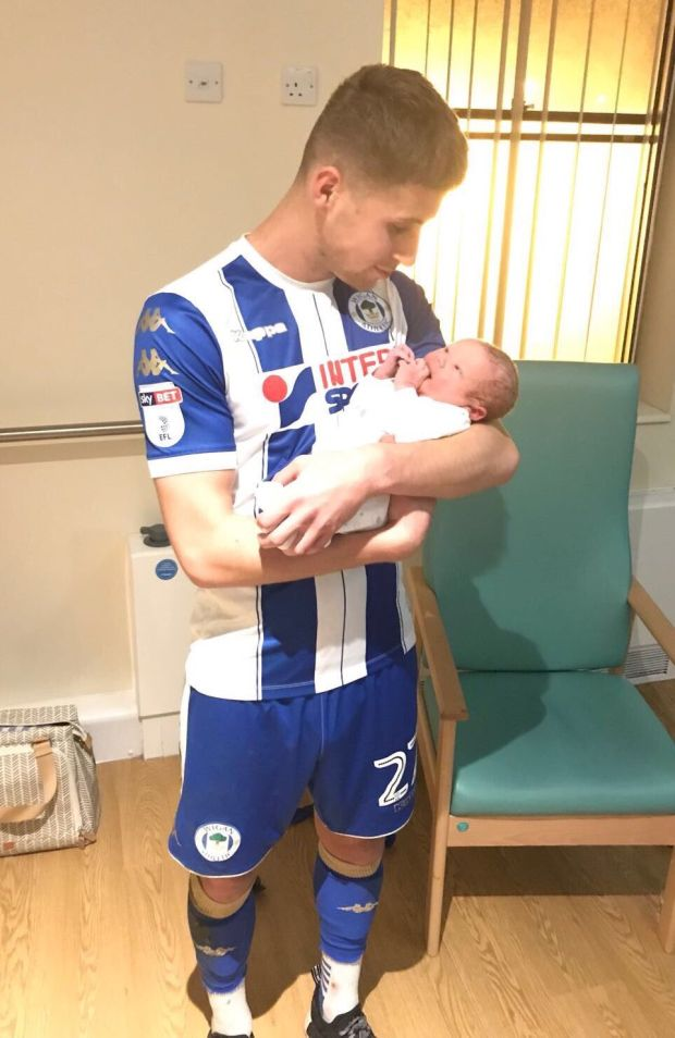 Ryan Colclough holds his newborn son Harvey Thomas while still wearing his full Wigan kit.
