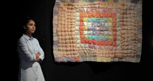 Mediator Aleksandra Amaladass interacting with the 'The Antibiotic Resistance Quilt' exhibit by British artist Anna Dumitriu. Photograph: Mark Stedman