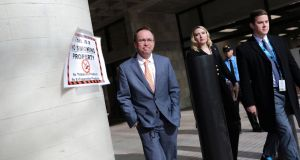 Mick Mulvaney (on left) leaves the Consumer Financial Protection Bureau  building in Washington on Monday. Photograph: Carlos Barria/Reuters