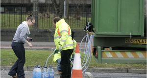 A householder collects water from a tanker due a boil-water notice. Photograph: Dara Mac Dónaill