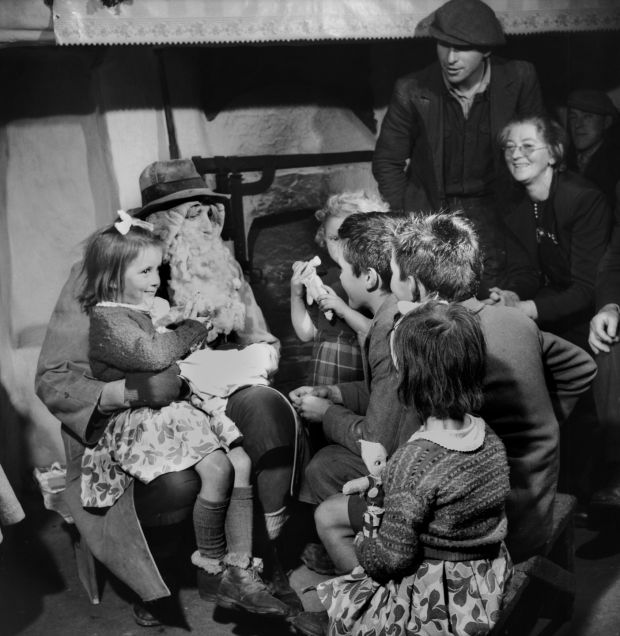 Children gather round to hear Santa Claus tell stories during Christmas in Ireland in 1955. Photograph: George Pickow/ Three Lions/Hulton Archive/Getty Images