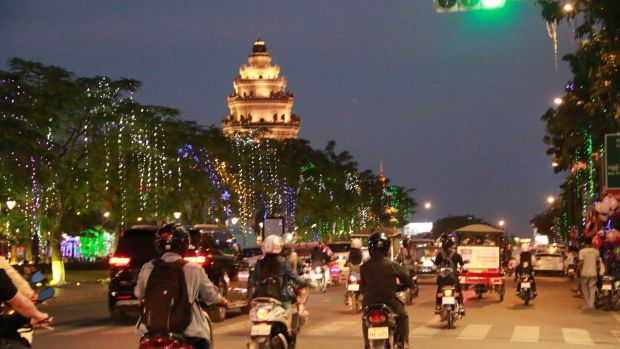 Motorists drive by the iconic Independence Monument in Phnom Penh. Photograph: Nevenka Lukin