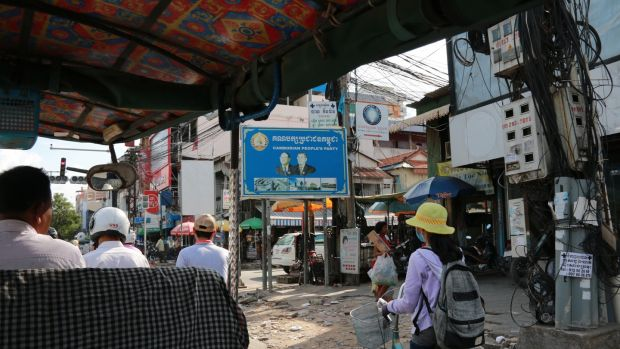 People pass a poster for the ruling Cambodia People's Party in Phnom Penh. Photograph: Nevenka Lukin